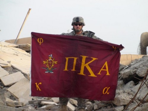 Holding the Pike flag up over the rubble of the house where Saddam's sons got killed.