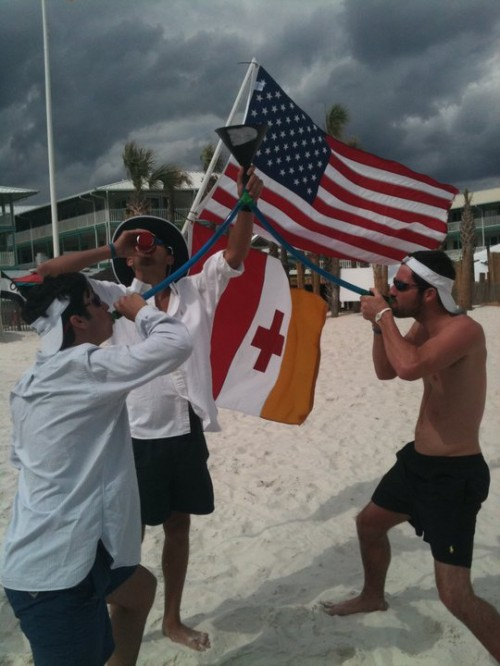 Funneling beers on the beach while our flags fly in the air. TFM.