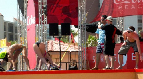 Calling the moves for a girl-on-girl game of Twister on the stage at Coca Cola Beach. TFM.
