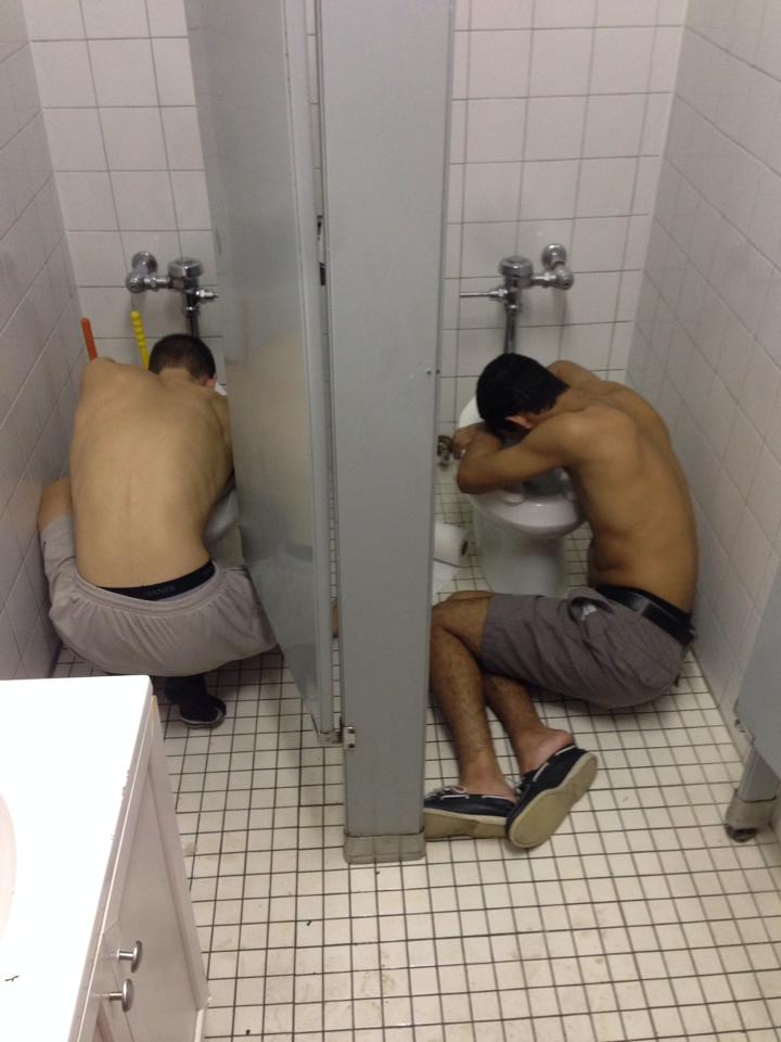 Brothers hug toilets together.