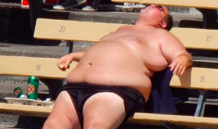 a fat man sprawled out on a bench